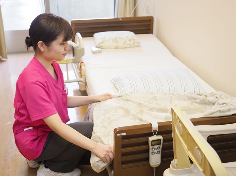 ベッドを整える小川さん